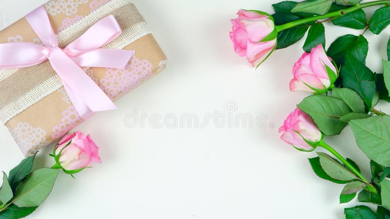 Mother`s Day overhead with gift and pink roses on white wood table background stock image
