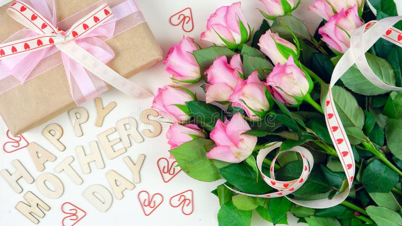 Mother`s Day overhead with gift and pink roses on white wood table background stock images