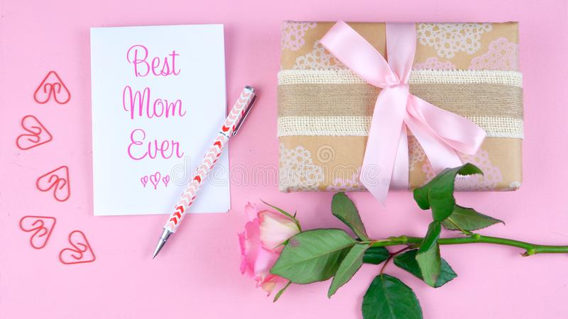 Mother`s Day overhead with rose, Best Mom Ever card and gift on pink table. royalty free stock image