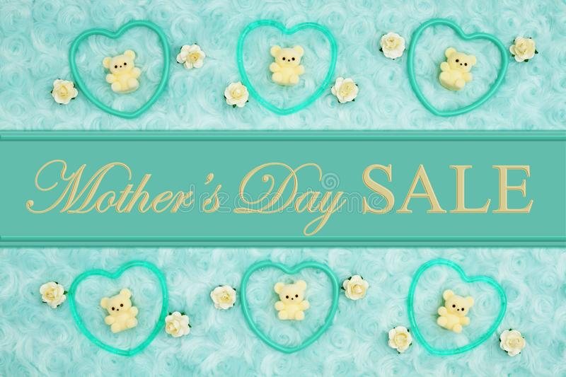 Mother`s Day Sale message with teal frame hearts, teddy bears and rose buds on a teal plush fabric. With ribbon royalty free stock image