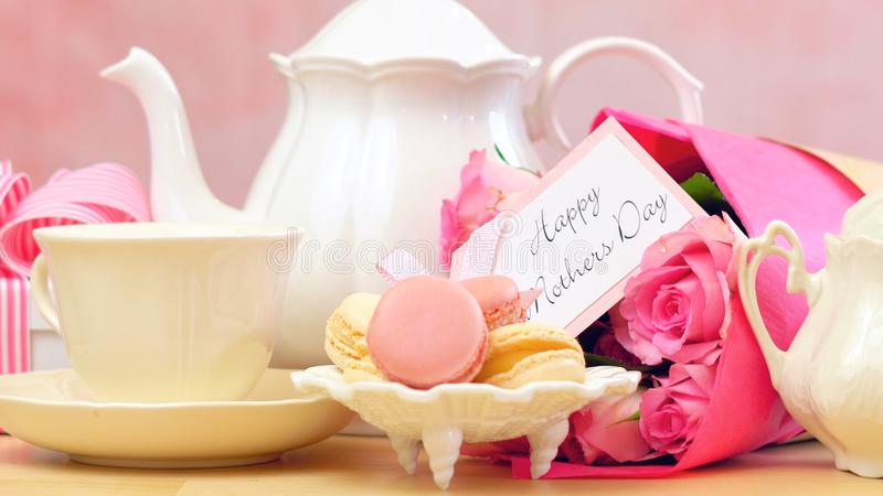 Mother`s Day tea setting with macaron cookies, pink roses and gift, closeup. stock photo