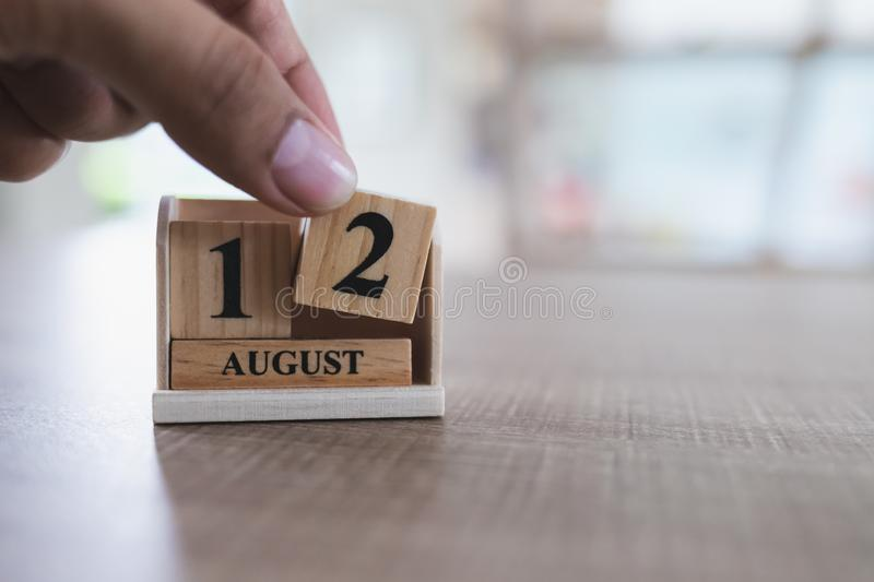 Mothert`s Day of Thailand, August 12, close up of left hand is picking up a wooden calendar block. That is placed on a wooden table and copy space royalty free stock images