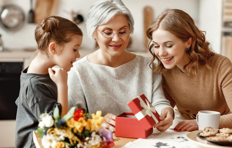 Mother`s day! three generations of  family mother, grandmother and daughter congratulate on the holiday, give flowers royalty free stock photography
