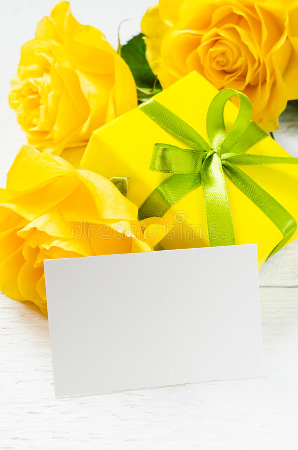 Mother`s day, Valentine`s or birthday concept. Present, roses and empty card. Mother`s day, Valentine`s or birthday concept. Present and yellow roses with empty stock photo