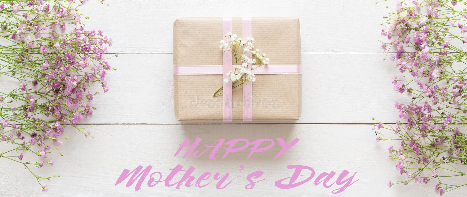 Mother`s day, white wooden table with pink flowers and a present royalty free stock images