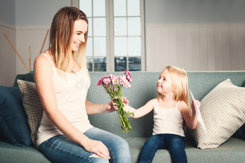 Mother`s Day. Woman and Child with Flowers and Gift Card. Smiling Daughter and Mother stock images
