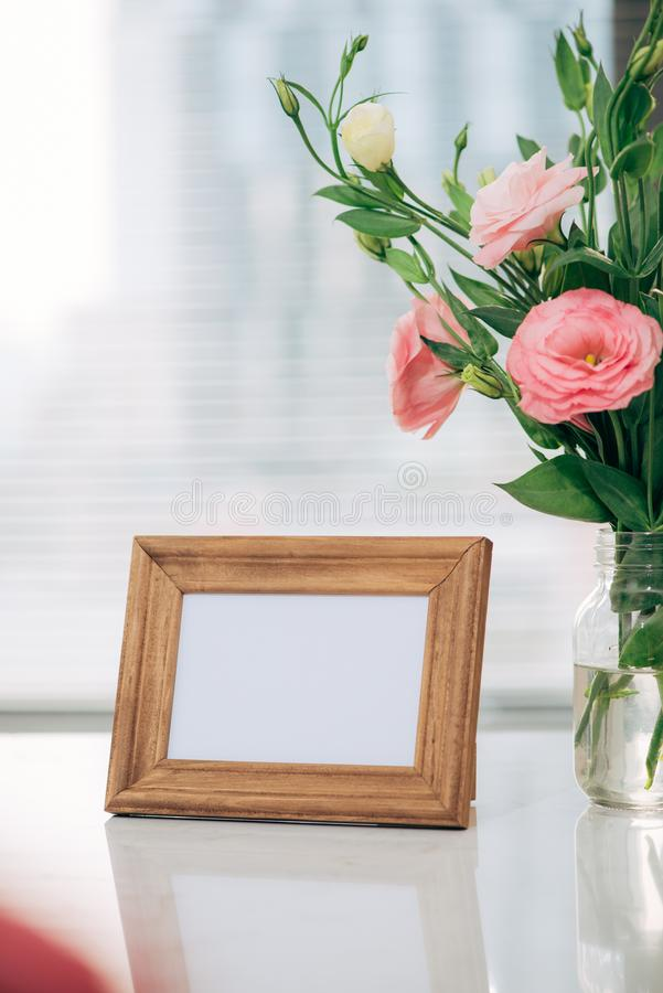 Wooden frame photo with pink flower in vase on table.hello summer or Monday morning concept and home decor.  royalty free stock photography