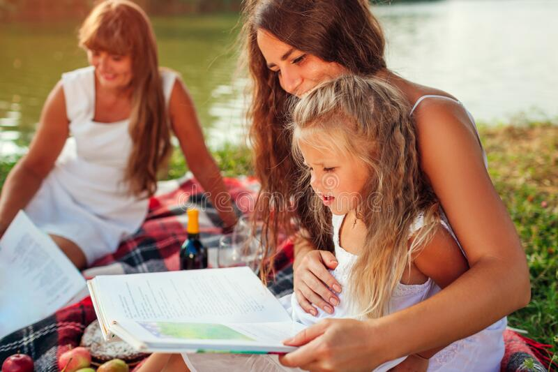 Mother`s day, Women`s day. Woman and her kids with grandmother reading books. Family having picnic in park. And having fun royalty free stock photos