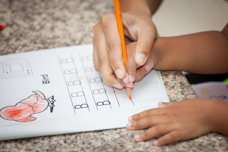 Mother's hand holding child hand writing her homework. With crayon royalty free stock photos