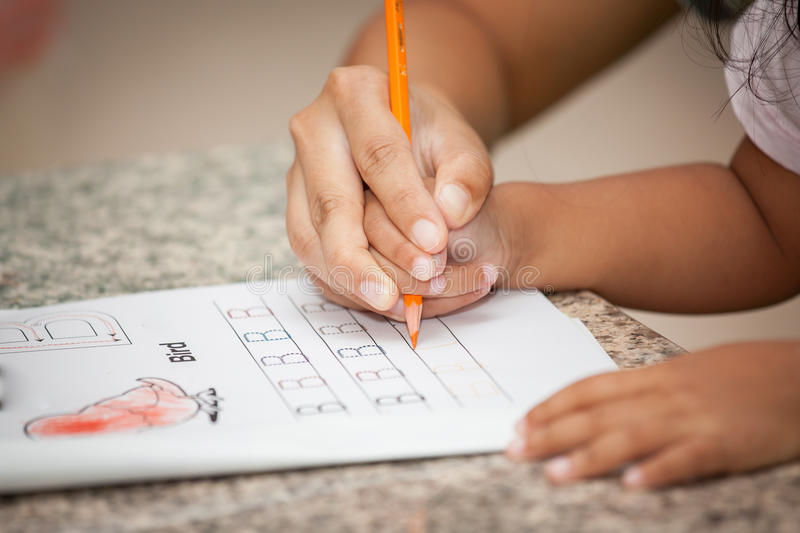 Mother's hand holding child hand writing her homework. With crayon royalty free stock images