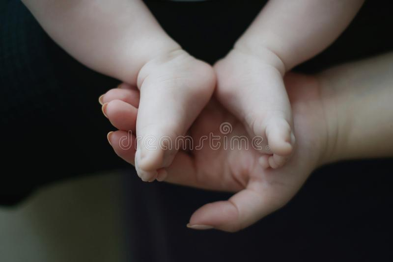 Mother`s hand holding gently tiny Caucasian baby feet and toes. Concept for families and generations, care for infants and newborn in early stages of their stock photo