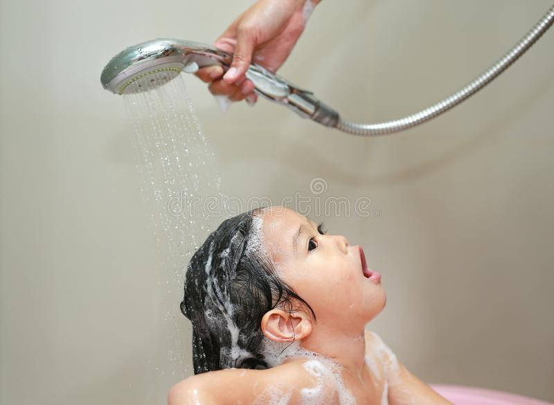 Mother`s hand pours water from shower to wash shampoo on little girl`s hair stock images