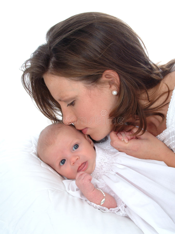 A Mother's Kiss. Newborn looking toward camera as mother kisses her
