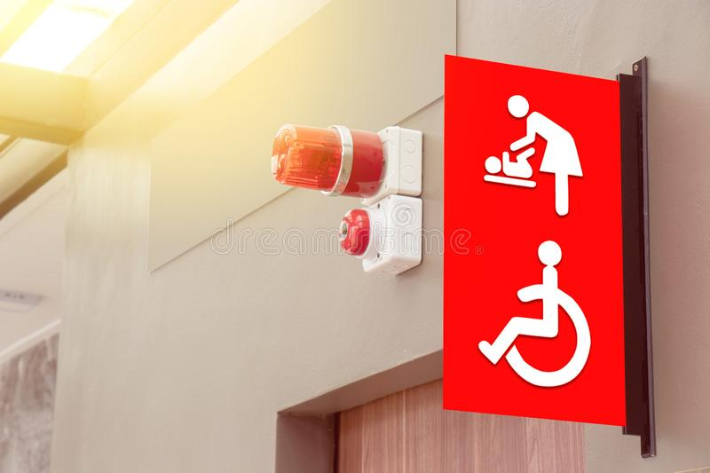 Mother`s room and disabled toilet sign on red tab with red siren light above the door of public toilet stock image
