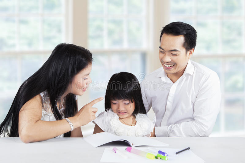 Mother scolding her child for doing school task. Beautiful young mother scolding her daughter to learn and doing school task at home stock photography