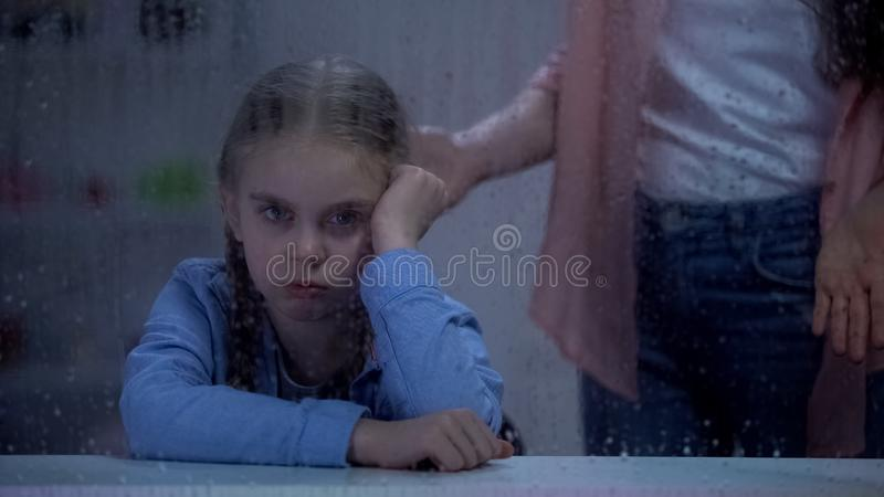 Mother scolding naughty little girl behind rainy window, problem child concept. Stock photo royalty free stock image