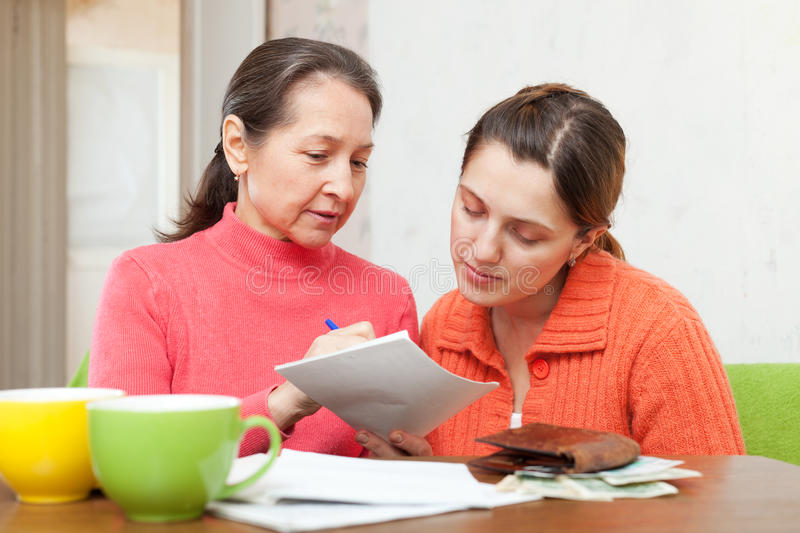 Mother scolds adult daughter for bills or credits. Mature mother scolds adult daughter for utility payments bills or credits royalty free stock image