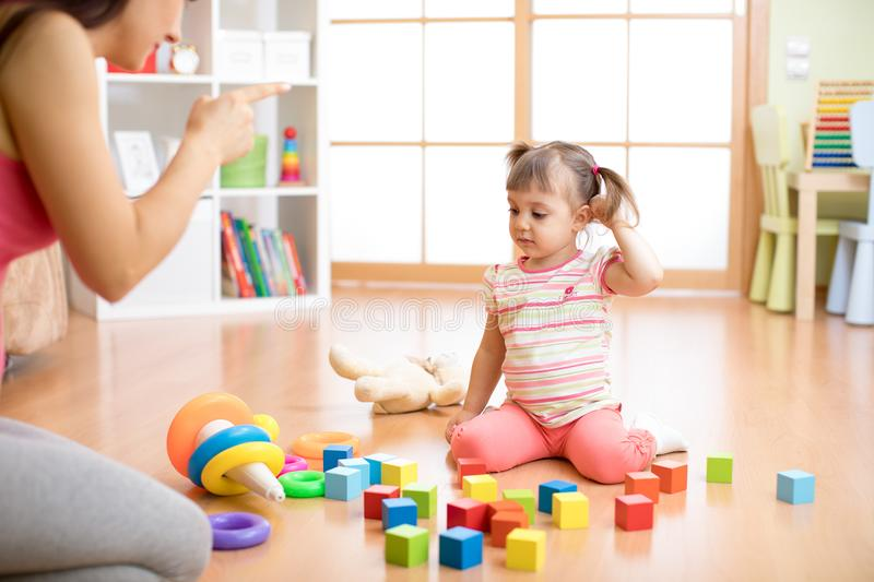Mother see her daughter play toys messy up the living room feel angry and criticize the sadness kid girl at home. stock photo