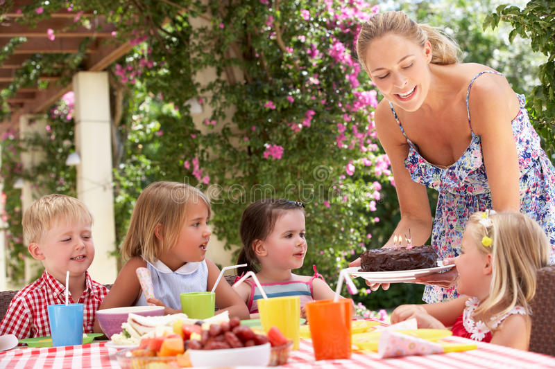 Mother Serving Birthday Cake To Group Of Children. Outdoors royalty free stock image