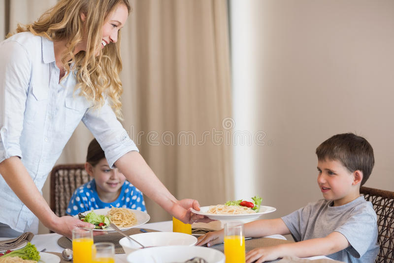 Mother serving pasta to son at dining table stock photo