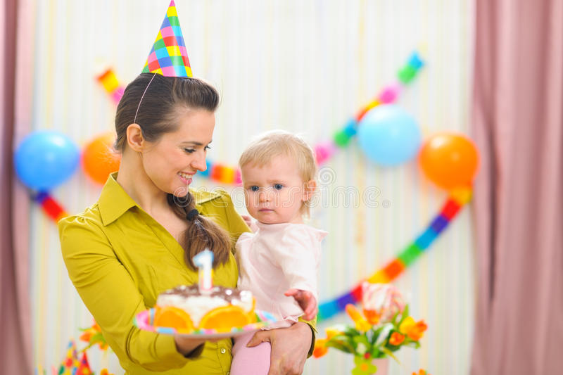 Mother showing baby birthday cake. Mother showing baby girl birthday cake royalty free stock image