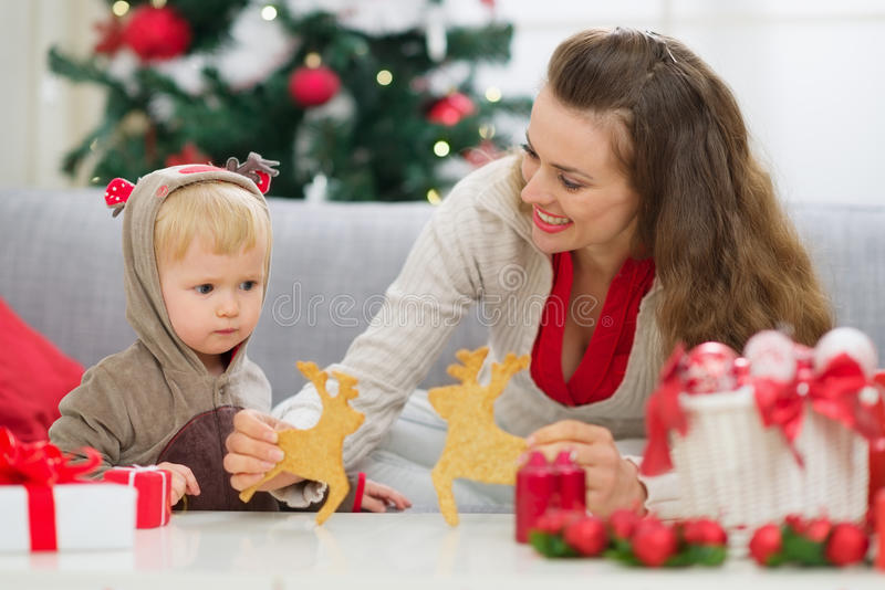 Mother showing baby Christmas deer shaped cookies royalty free stock images