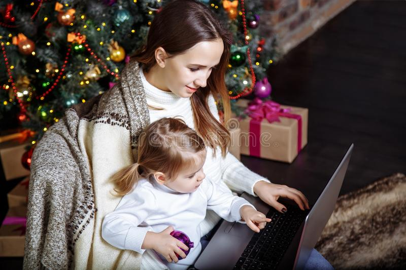 Mother showing baby something in laptop near Christmas tree stock photo
