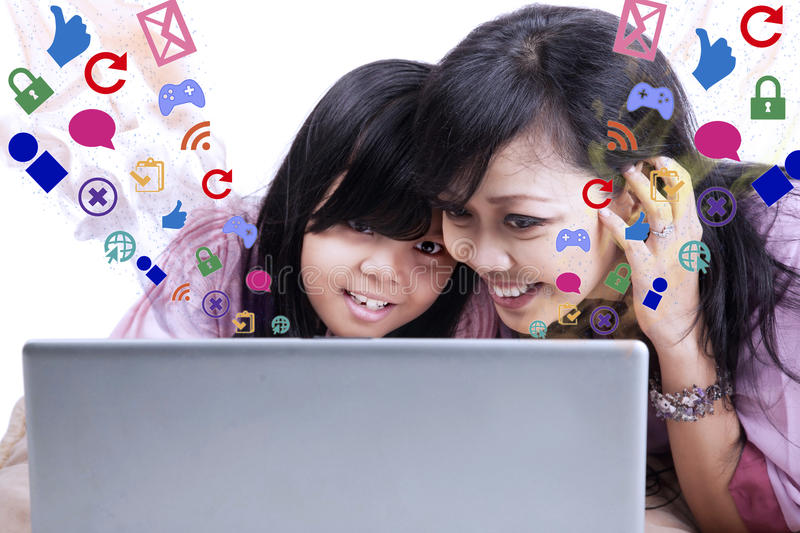 Mother showing e-mail on laptop to daughter. Asian mother and mother looking at their laptop. Shot in studio isolated on white royalty free stock image