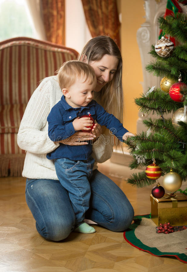 Mother showing her baby son how to decorate Christmas tree with stock image