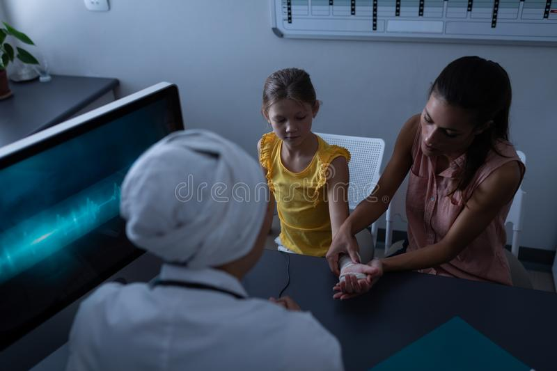 Mother showing her daughter fractured hand to doctor in clinic. Rear view of Caucasian mother showing her Caucasian daughter fractured hand to mixed race female stock image