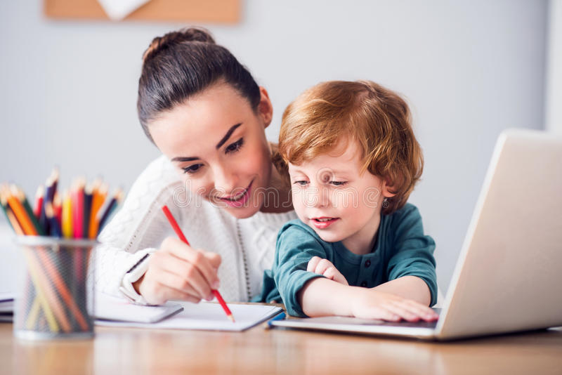 Mother showing how to draw. Source of inspiration . Young pretty women showing to her little son how drawing while sitting in front of a laptop stock photo