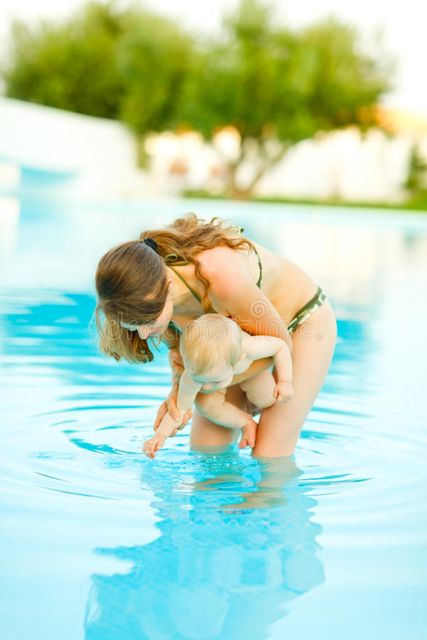 Mother showing water to baby standing in pool royalty free stock photos