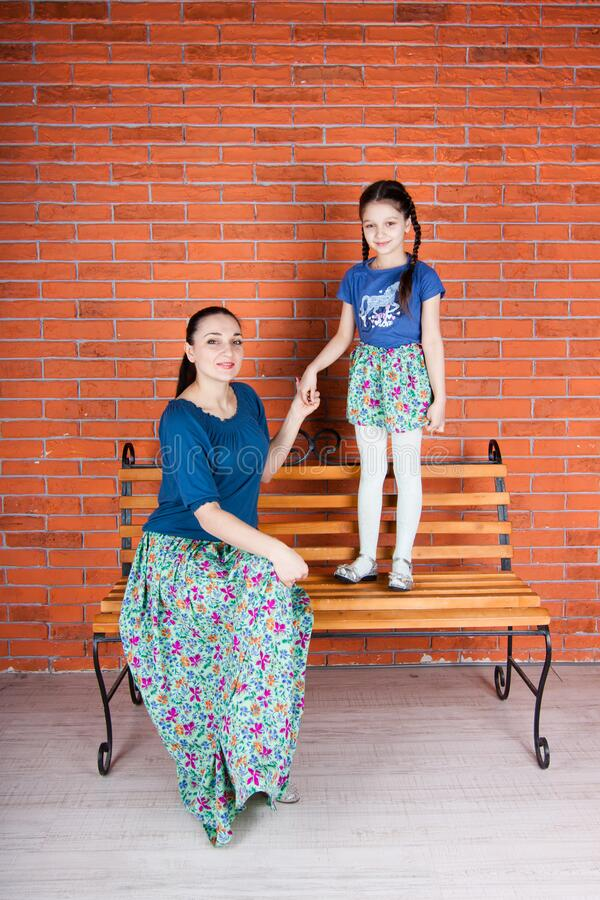 Mother sits on the bench and daughter stays in front of red brick wall. stock image
