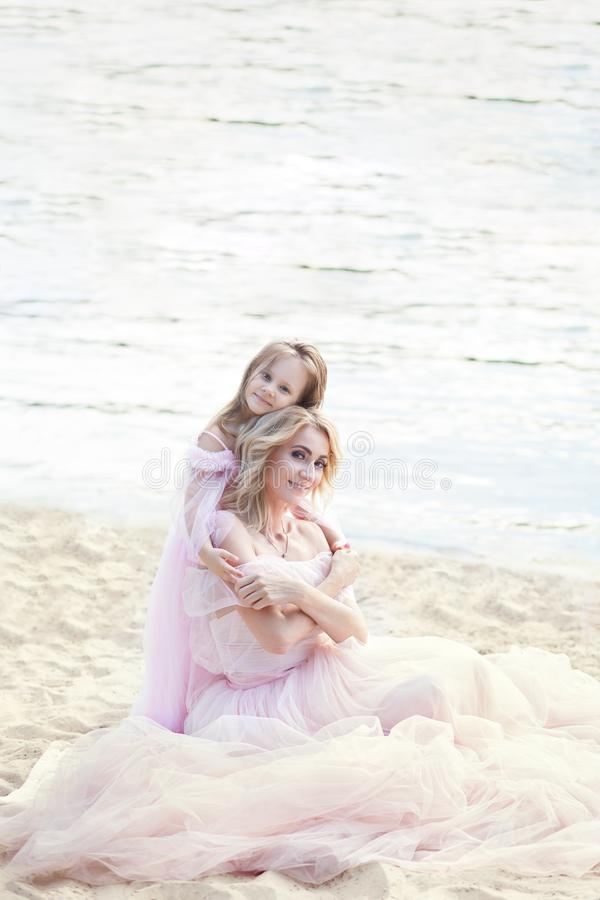 Mother sitting on the beach with a beautiful little girl. Child hugging, smiling, laughing, summer day. Happy childhood carefree g stock images