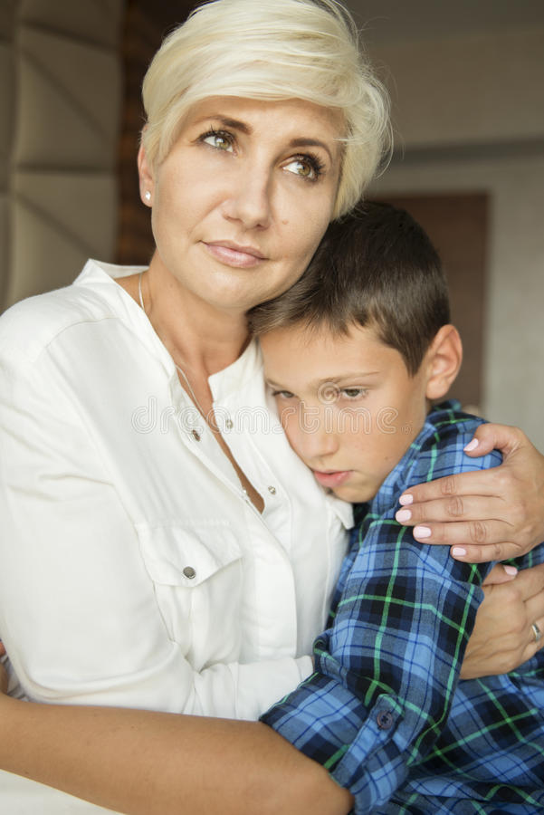 Mother sitting on a bed and cuddling her sad son royalty free stock image