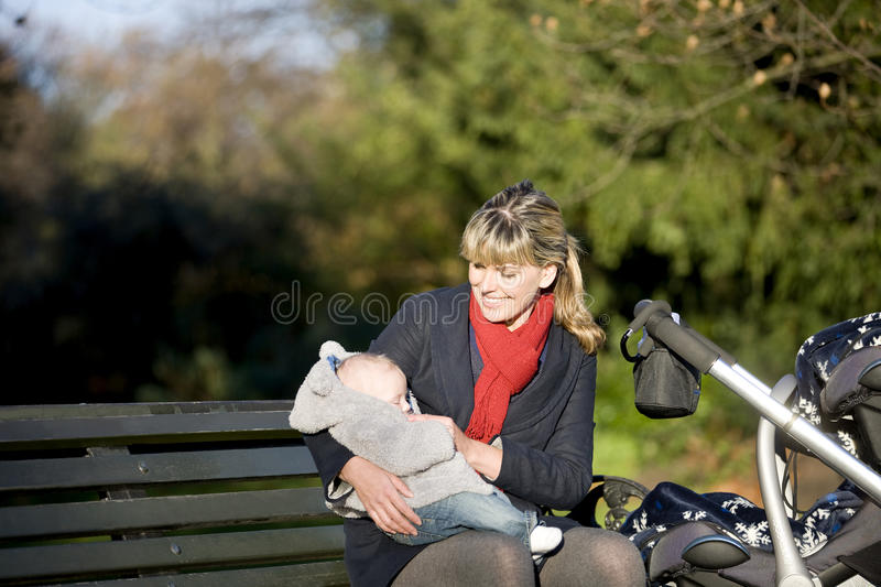 A mother sitting on a bench, holding her baby on her lap royalty free stock photo
