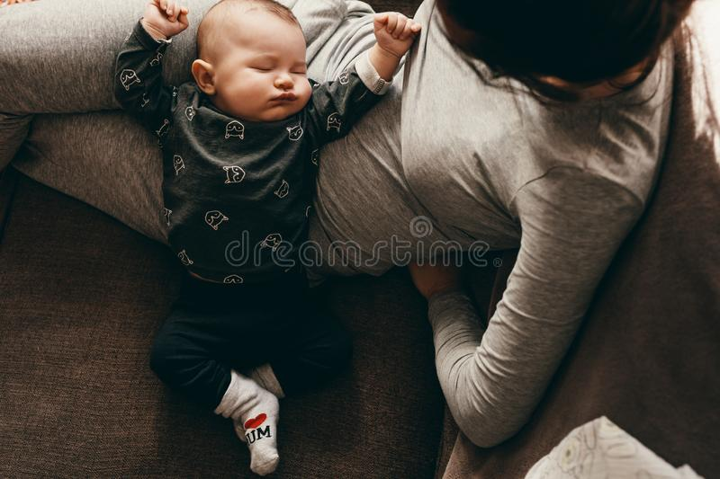 Mother sitting on couch with her baby sleeping on her. Top view of a baby sleeping in the lap of his mother. Close up of a women sitting on a couch putting her royalty free stock image
