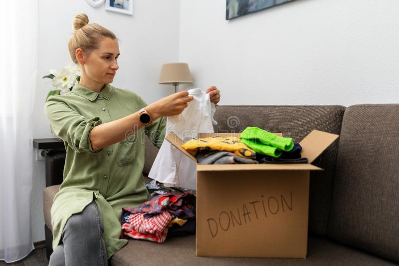 Mother sitting on couch and sorting child clothes for donation. Mother sitting on couch at home and sorting child clothes for donation stock image