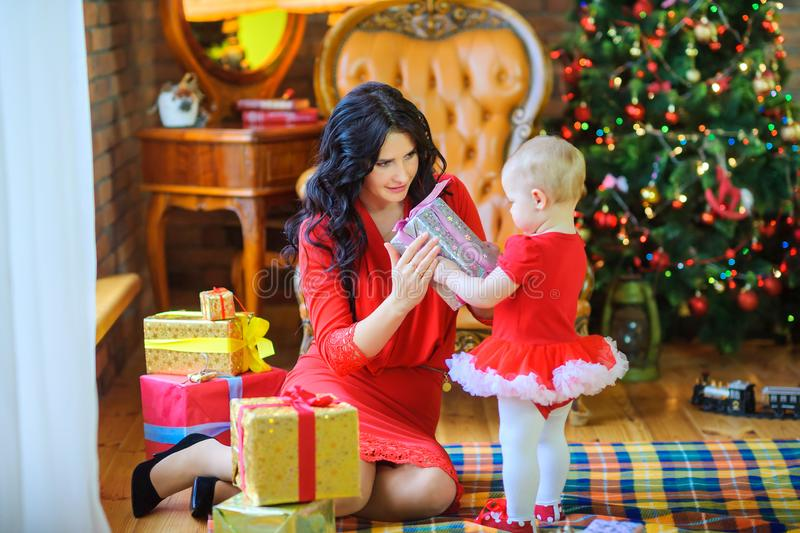 Mother sitting on the floor near the Christmas tree gives a gift to her beloved daughter royalty free stock photos