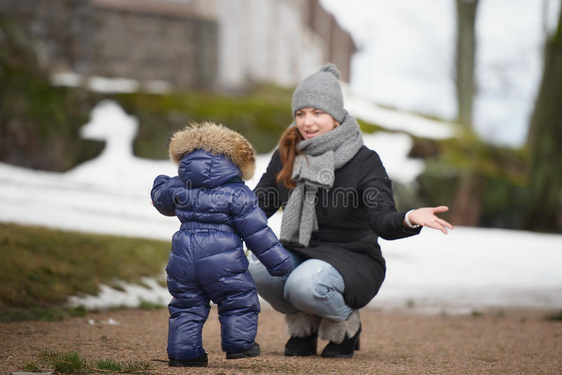 Mother sitting in front of her child who is walking to her stock photo