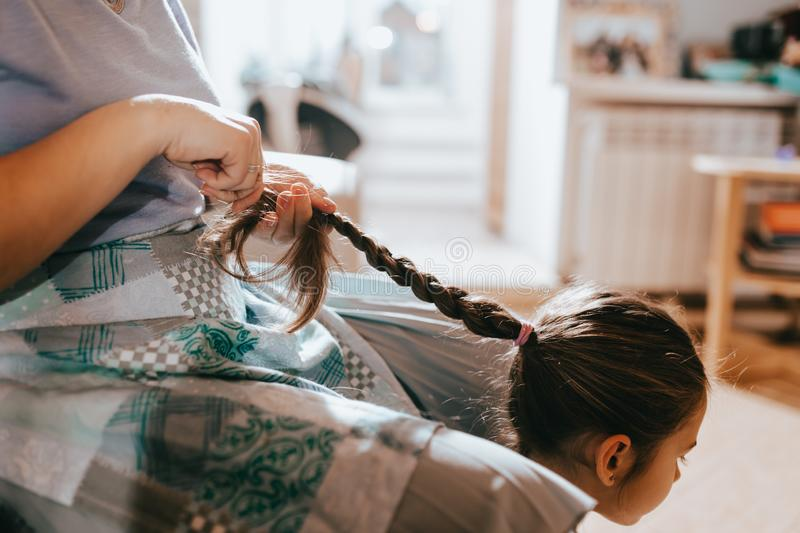 Mother sitting on the sofa braids her daughter`s hair sitting on the floor next to her in the cozy light room stock images