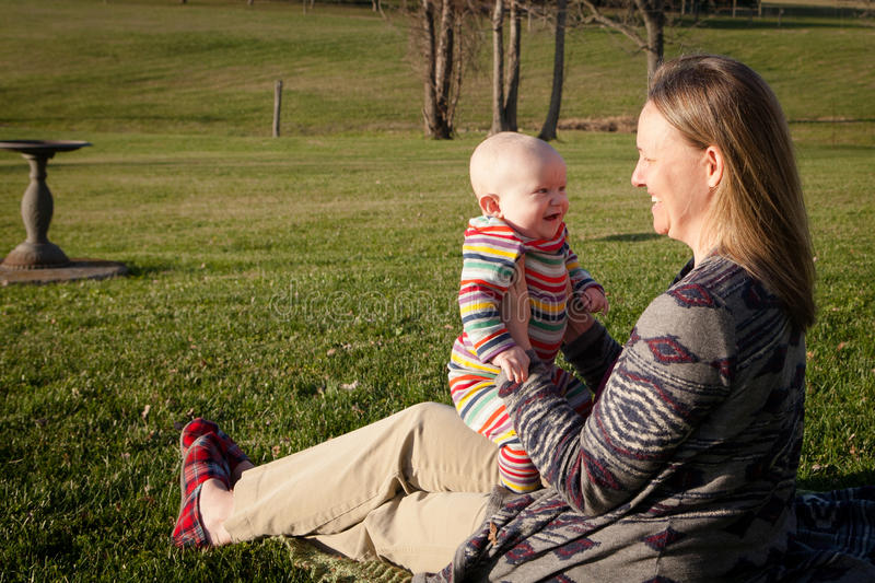 Mother Sitting with Son Outside stock images