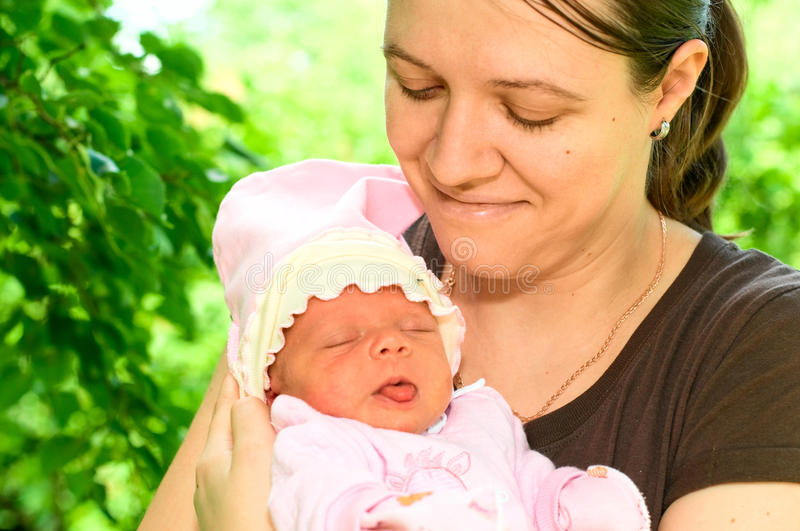 Mother with sleeping baby. Portrait of mother with child outdoors stock photography