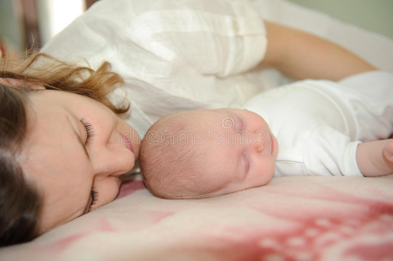 Mother sleeping with baby. Young mother is sleeping with her little baby stock photo