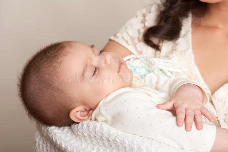Mother with sleeping baby portrait, happy maternity concept, yellow toned royalty free stock images