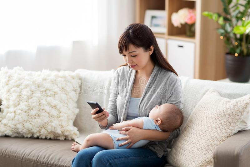 Mother with sleeping baby and smartphone at home. Family, technology and motherhood concept - happy young asian mother with sleeping baby and smartphone at home stock images