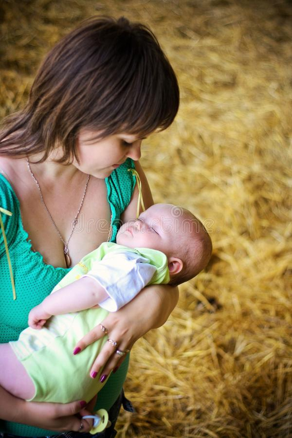 Mother with sleeping child on hands. Happy young mother with sleeping child on hands stock photos