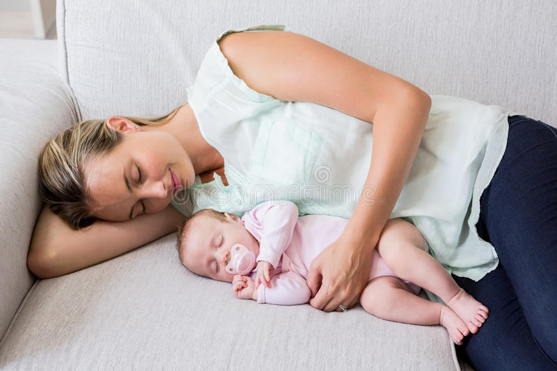 Mother sleeping with her baby in living room. At home stock photo
