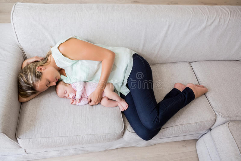 Mother sleeping with her baby in living room. At home royalty free stock photo