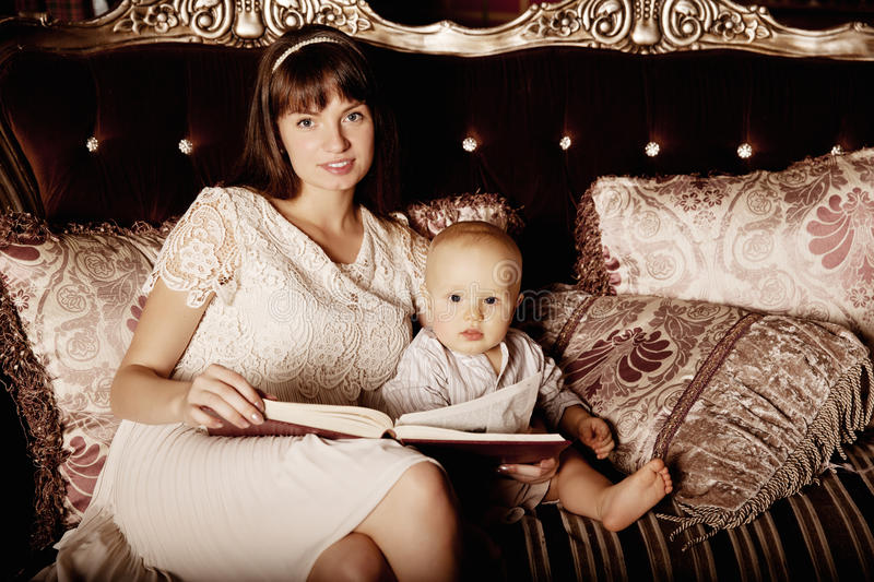 Mother with a small child in the interior reading a book together. Smiling family in the bedroom reading a book. Mom and baby on stock photography
